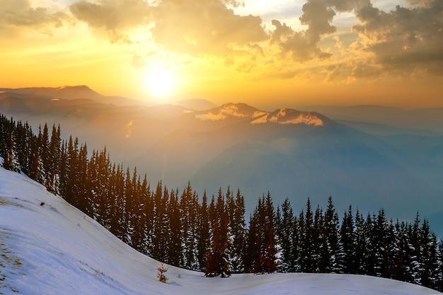 Zimowy krajobraz z wysokimi szczytami i mglistą doliną pod żywym kolorowym niebem o zachodzie słońca w górach skalistych.