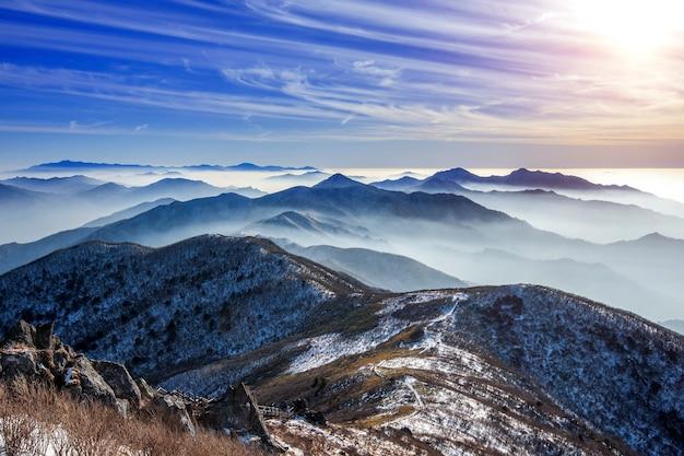 Zimowy krajobraz z zachodem słońca i mglisty w górach deogyusan, korea południowa