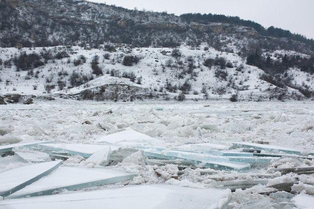 Zimowy krajobraz zamarzniętej rzeki z wieloma dużymi kry lodowymi. piękny krajobraz.