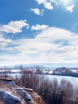 Zimowy krajobraz ze skałą, rzeką i malowniczym niebem