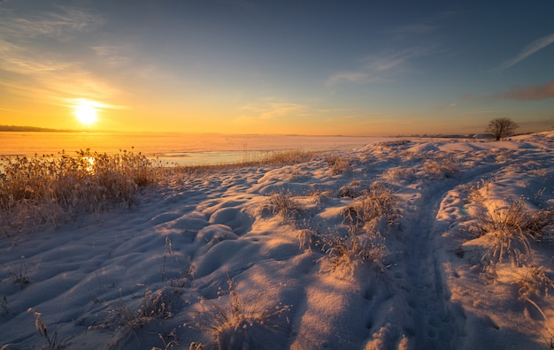 Zimowy krajobraz ze śniegiem, oceanem, morzem, niebieskim niebem, drogą, światłem słonecznym, lodem.