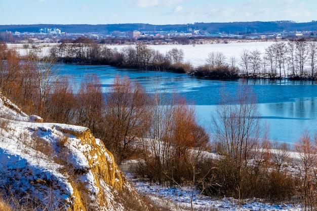 Zimowy krajobraz ze śnieżną skałą i rzeką przy słonecznej pogodzie
