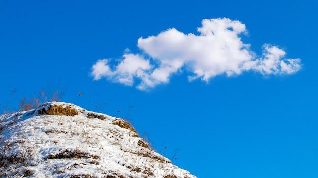 Zimowy krajobraz ze śnieżnym wzgórzem i białą chmurą na niebieskim niebie