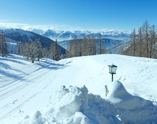 Zimowy mglisty widok z masywu górskiego dachstein w austrii i lampka w pobliżu wejścia do hotelu