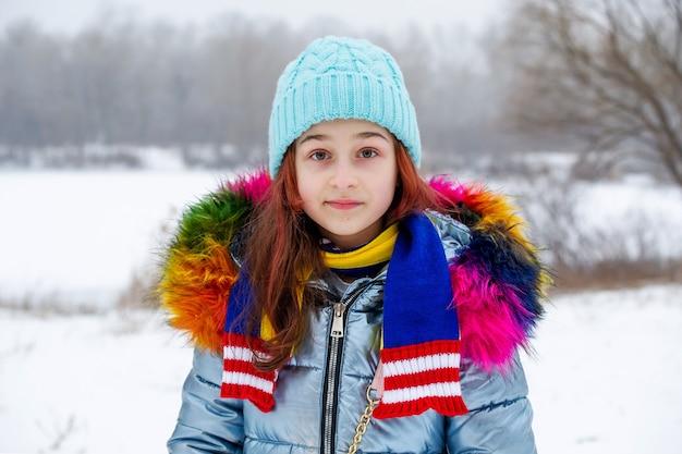 Zimowy. młoda dziewczyna w ciepłej odzieży. nastolatka w niebieskim kapeluszu i szaliku w śnieżnej pogodzie. dziecko