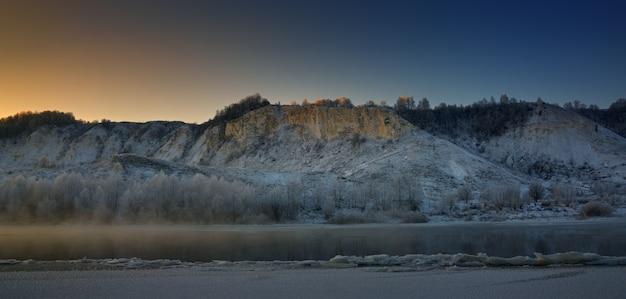Zimowy mroźny poranek przed świtem. marznąca rzeka z pagórkowatych brzegów i duże kry lodowe.