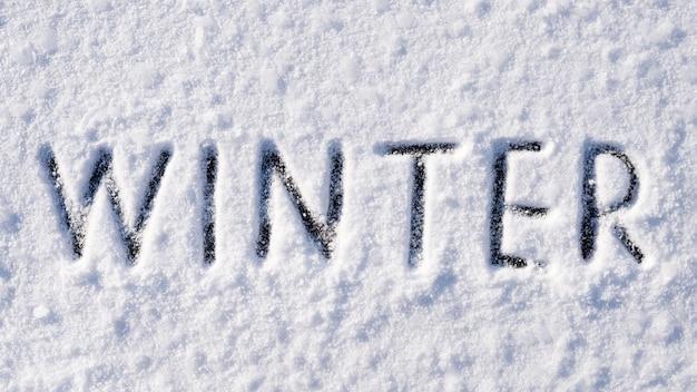 Zimowy napis na białej powierzchni śniegu