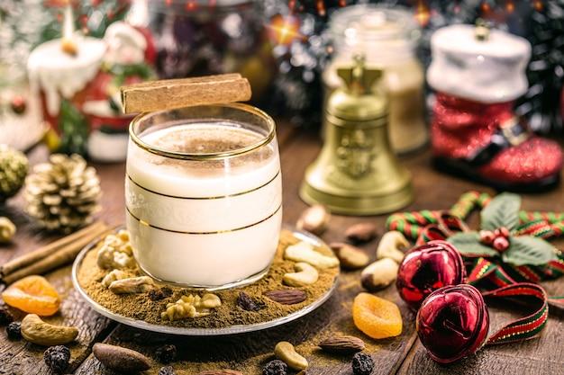 Zimowy napój z jajek, likieru i cynamonu, zwany ajerkoniakiem, coquito lub mlekiem auld mana, ozdobiony orzechami i suszonymi owocami