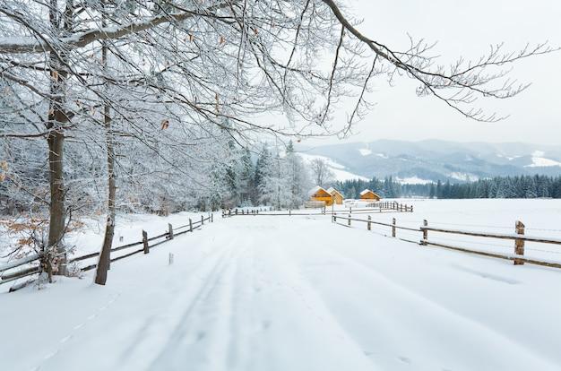 Zimowy nudny kraj górski krajobraz z ogrodzeniem i lasem jodłowym