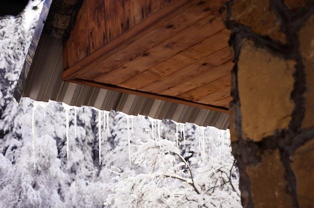 Zimowy pejzaż z lodowymi soplami zwisającymi z dachu domu.
