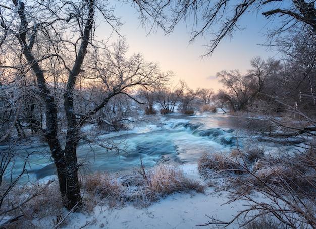 Zimowy pejzaż z ośnieżonymi drzewami, piękna zamarznięta rzeka o zachodzie słońca