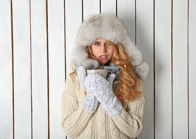 Zimowy portret młodej pięknej blond kobiety w ciepłą odzież z dzianiny, z kubkiem gorącego napoju