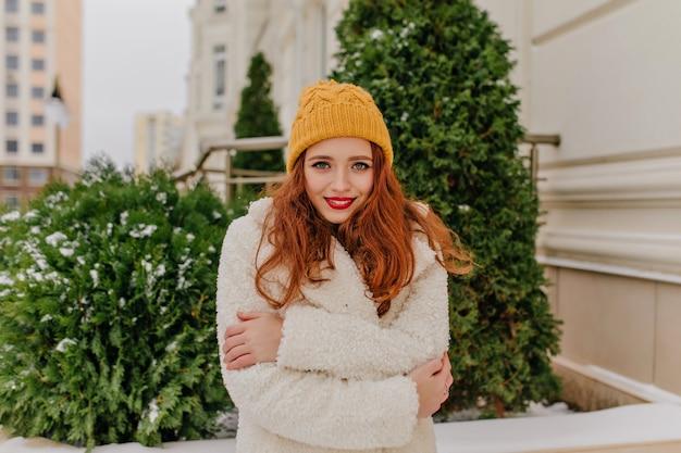Zimowy portret nieśmiała dziewczyna imbir. plenerowe zdjęcie europejki nosi kapelusz i płaszcz.