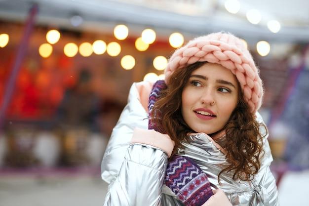 Zimowy portret pięknej brunetki młodej damy sobie ciepły modny strój, spacerując na jarmarku bożonarodzeniowym w kijowie. miejsce na tekst