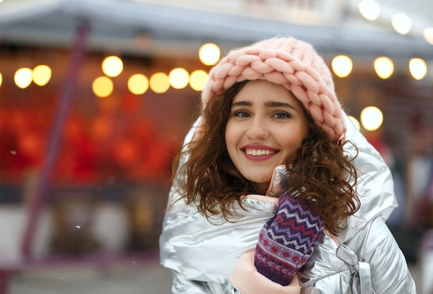 Zimowy portret pozytywnej brunetki młodej damy sobie ciepły modny strój, spacerując na jarmarku bożonarodzeniowym w kijowie. miejsce na tekst