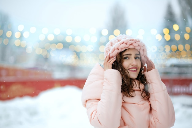 Zimowy portret stylowej brunetki młodej damy sobie ciepły modny strój, spacerując na jarmarku bożonarodzeniowym w kijowie. miejsce na tekst