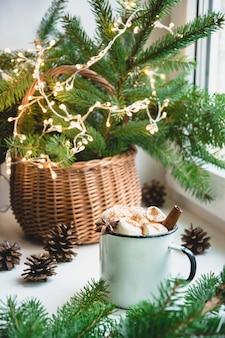Zimowy rozgrzewający kubek czekolady z pianką na parapecie.