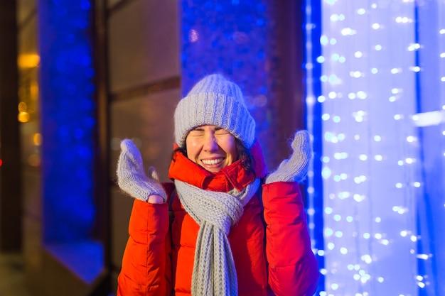 Zimowy sezon wakacyjny. boże narodzenie, koncepcja nowego roku. śmieszna szczęśliwa kobieta spędza czas na zabawie w pobliżu oświetlonej i ozdobionej gabloty na ulicy miasta.
