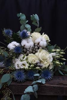 Zimowy ślubny bukiet białych róż, bawełny i eringium na czarnym tle. bukiet panny młodej