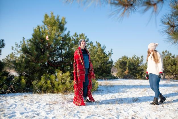 Zimowy spacer po lesie. facet w czerwonej szkockiej kracie pozuje jak superbohater, biorąc pod uwagę, że szkocka krata jest jego płaszczem. superbohater, na który zasługujemy