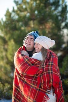 Zimowy spacer po lesie. facet w czerwonym kocu w kratę otula dziewczynę, żeby się rozgrzała.