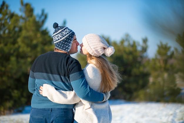 Zimowy spacer po lesie. widok z tyłu faceta z dziewczyną w objęciowym spacerze w zimowym lesie