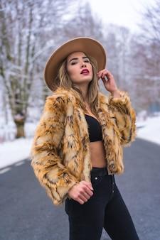 Zimowy styl życia, modelka ciesząca się w bieliźnie, kowbojskim kapeluszu i swetrze lamparta na środku drogi z zamarzniętymi drzewami w tle