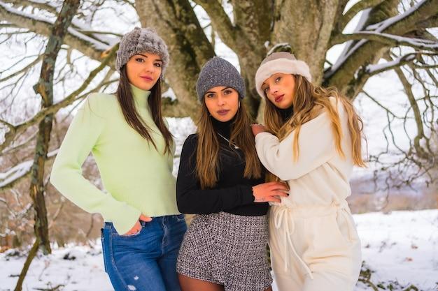 Zimowy styl życia, trzech pięknych kaukaskich przyjaciół korzystających ze śniegu zimą pod drzewem, wakacje na łonie natury