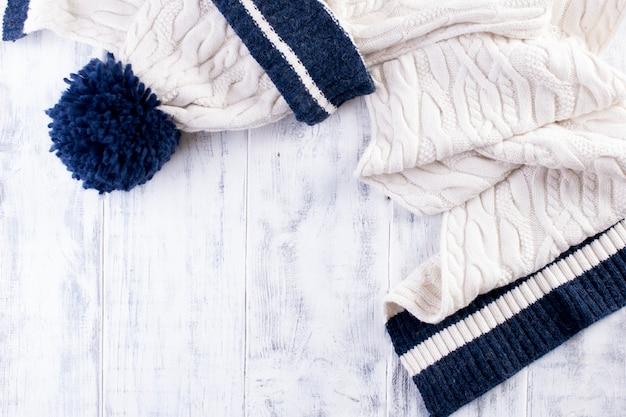 Zimowy szal z dzianiny i białą czapkę z niebieskim paskiem na białym tle drewnianych. skopiuj miejsce na tekst happy new year greeting card winter theme