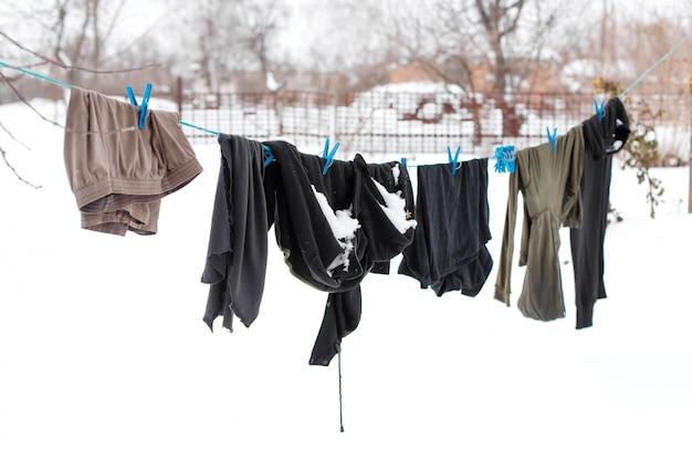 Zimowy. ubrania wysychają na ulicy. ubrania pokryte śniegiem schną na napiętej linie.