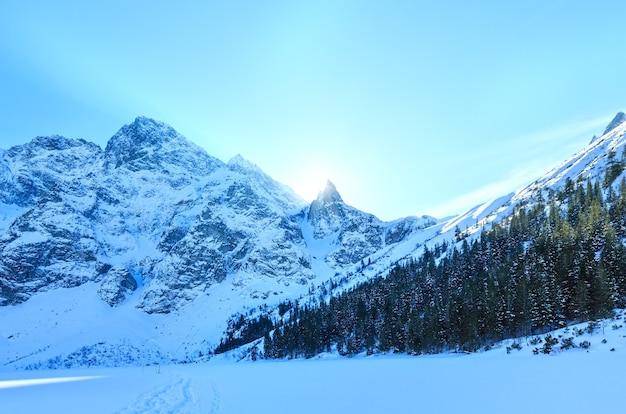 Zimowy widok na skaliste góry z promieni słonecznych zza skał i jodłowego lasu na zboczu.