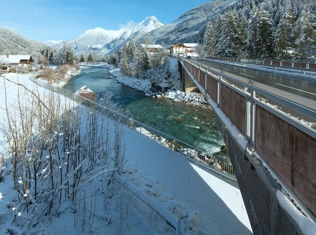 Zimowy widok na wieś haselgehr z rzeką lech (austria, tyrol)