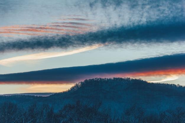 Zimowy wieczór malowniczy krajobraz ze wzgórza i pochmurnego nieba