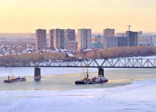 Zimowy wieczór na moście kolejowym ob przeprawia się przez pokrytą lodem rzekę