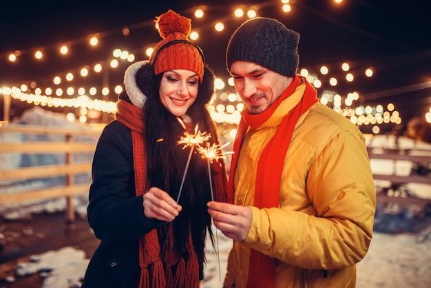 Zimowy wieczór, zakochana para całuje się z ogniskami