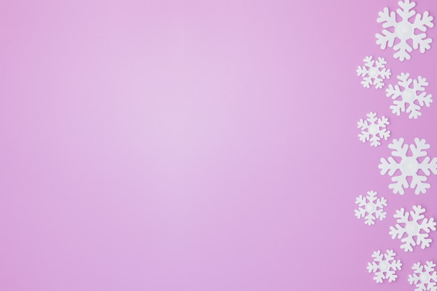 Zimowy wzór ze śniegu i na różowym tle.