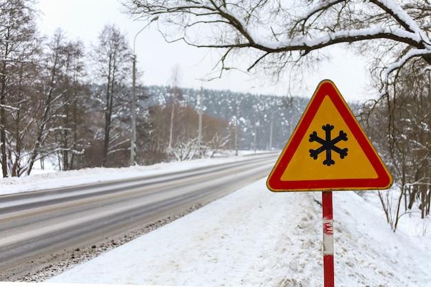 Zimowy znak ostrzegawczy wskazuje niebezpieczeństwo lodu i śniegu na ulicy, autostradzie lub drodze. jazda zimą. tymczasowe znaki drogowe na drodze. ryzyko śniegu i lodu.