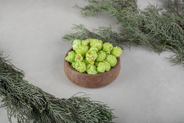 Zimozielone gałęzie drzew z miską cukierków popcornowych pośrodku na marmurowym stole.