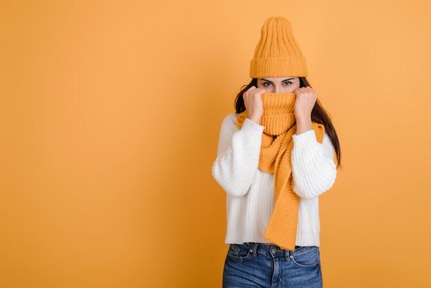 Zimy kobieta z pięknymi oczami jest ubranym szalika zakrywającego jej usta i nos