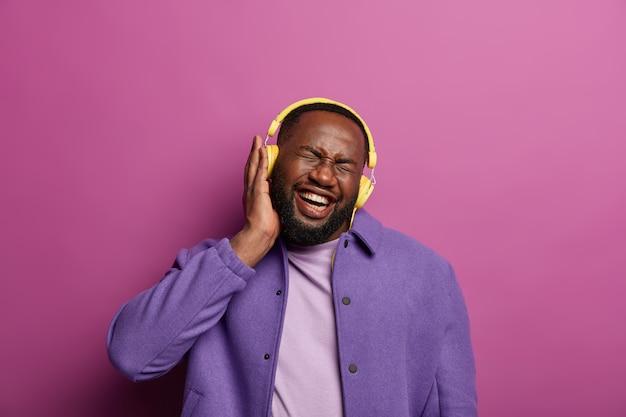 Zintegrowany, uszczęśliwiony hipster słucha głośnej muzyki w żółtych słuchawkach, śmieje się i zamyka oczy, zapomina o wszelkich problemach
