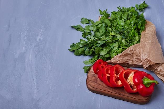 Zioła i chili na drewnianej desce na niebiesko