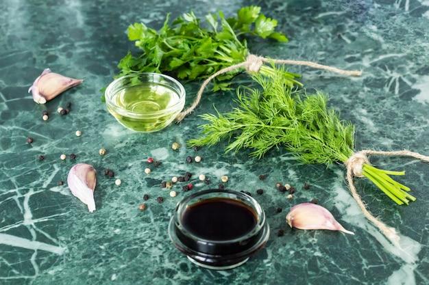 Zioła i przyprawy na marmurowym stole z kamienia. pietruszka, koperek, czosnek, oliwa z oliwek, sos sojowy i pieprz