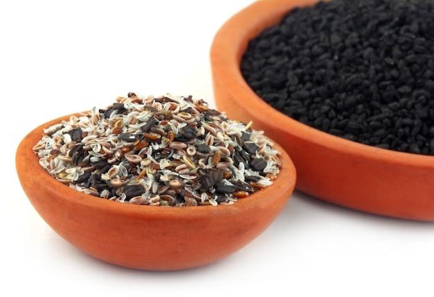Zioła lecznicze isabgul, nasiona bazylii i czarnuszka na glinianym garnku na białym tle