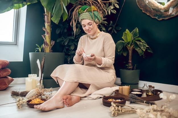 Zioła lecznicze. uśmiechnięta młoda dorosła kobieta z wysoką fryzurą boso, siedząca na podłodze w pokoju, przygotowująca ziołową mieszankę