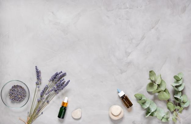 Zioła medycyny alternatywnej, oleje i kamienie na szarym tle.