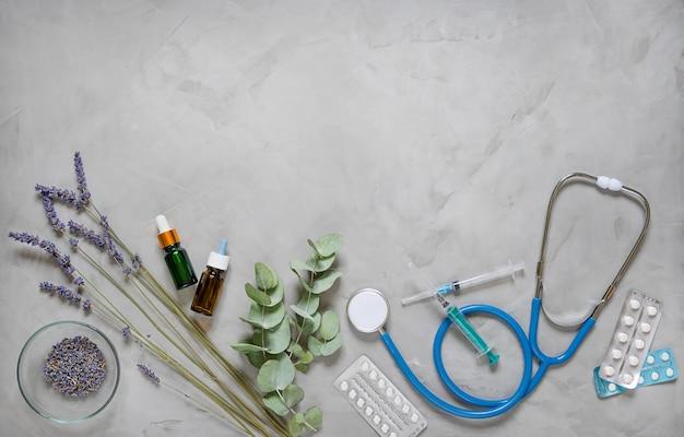 Zioła medycyny alternatywnej, oleje i stetoskop na szarym tle.