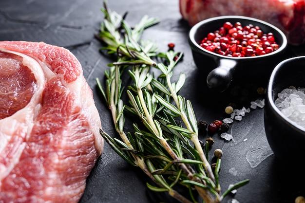Zioła rozmarynu z bliska na czarnym kamiennym stole z przyprawami i surowym mięsem w pobliżu widoku z boku selektywnej ostrości