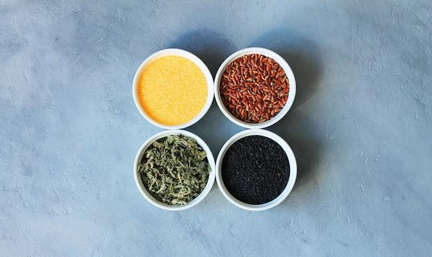 Zioła, zboża i nasiona w misce na szarym tle betonu