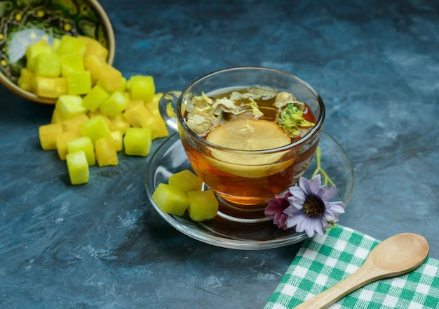 Ziołowa herbata cytrynowa z kostkami cukru, łyżką, ręcznikiem w filiżance na ciemnoniebieskiej powierzchni, wysoki kąt widzenia.