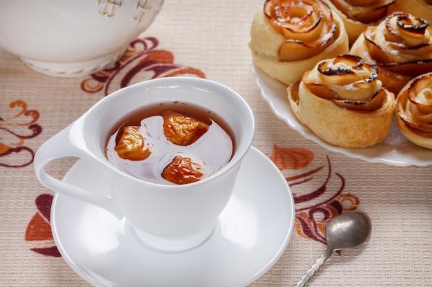 Ziołowa herbata jabłkowa w białej filiżance ze spodkiem i rumianymi bułeczkami na